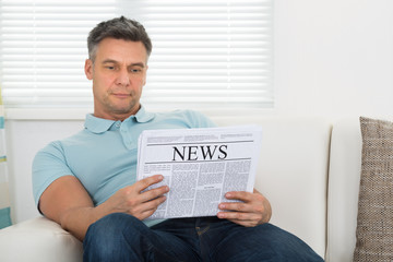 Man Reading Newspaper Sitting On Sofa