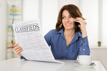 Woman Holding Newspaper While Talking On Mobile Phone