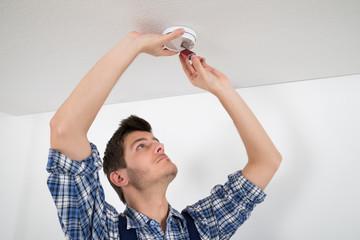 Electrician Repairing Smoke Detector