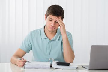 Unhappy Man Calculating Tax