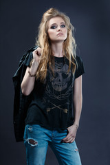Portrait of a charismatic female rocker with a leather jacket thrown back across the arm of