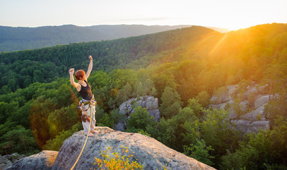 Young woman climber standing on mountain peak with raised arms and celebrating her success, looking to the sun. Warm sunny evening in the mountains. Climbing equipment.