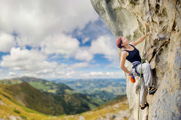 Young athletic female rock climber climbing cliff wall, hanging on one hand and holding hand in magnesium bag. Mountains and blue sky on the background. Copy space on the left.