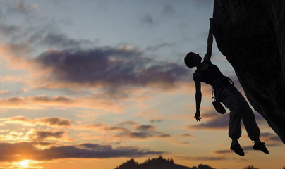 Silhouette of athletic woman rock climber climbing steep rock wall against amazing sunset sky in the mountains on high altitude. Girl is hanging on one hand