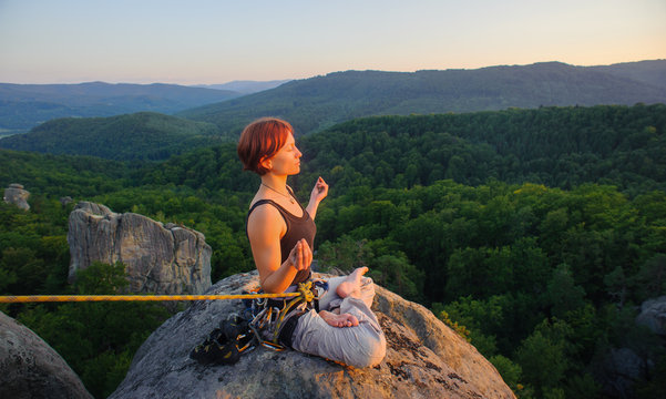 Young athletic girl climber sitting secured with rope and meditating with crossed legs on high mountain summit. Beautiful sunset in the mountains.