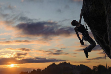 Silhouette of athletic woman rock climber climbing steep rock wall with rope against amazing sunset sky in the mountains. Girl is hanging on one hand and holding hand in magnesium bag.