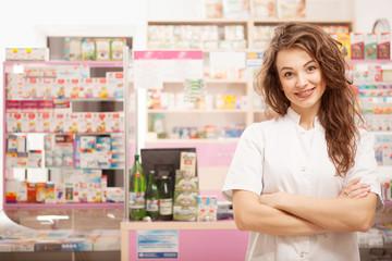 Smiling doctor in front of pharmacy desk