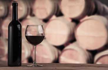 Red wine bottle with glass on the background of oak barrels. Wine background