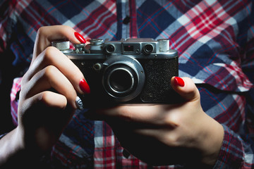Closeup of retro camera in hipster girl hands