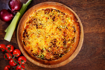 Pizza with beef stuffing, leek and cheese served on wooden table