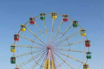 Ferris wheel with color cabins against the blue sky