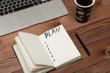 Notebook with business plan, phone, laptop. coffee cup on table