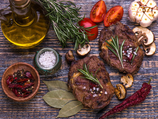 Beef steak with herbs and rosemary, fresh juicy on a wooden table background. Seleсtive focus