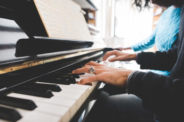 Close up on the hands of young handsome man playing piano with h