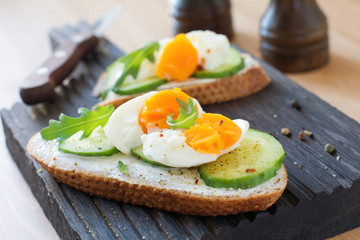Cucumber and egg toast with arugula and cream cheese. Tasty breakfast or snack on wooden cutting board. Selective focus