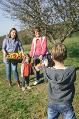 Boy taking photo to family with apples in basket