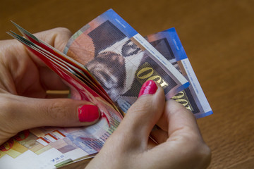 Woman counting money - Israeli New Sheqel banknotes.