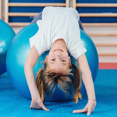 Little girl at physical education class, stretching over fitness ball