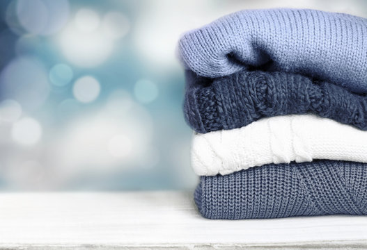 Pile knitted winter autumn clothes on wooden background.
