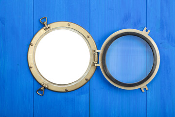 Brass porthole in blue wooden wall, opened, with clipping path