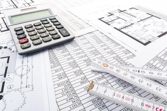 Taschenrechner und Zollstock auf Tabellen und Hausgrundrissen