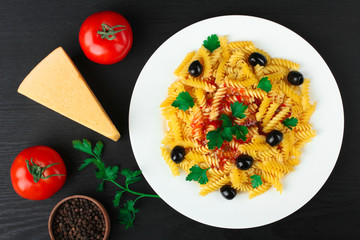 fusilli pasta and olives in the dish by the fresh tomatoes and peppers with garlic and cheese with parsley lay on a wooden black background