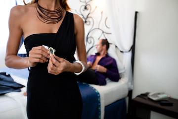 femme debout avec un préservatif  avec un homme allongé sur un lit