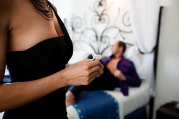 femme avec un préservatif devant un homme couché