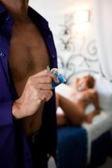 homme avec un préservatif devant une femme nue
