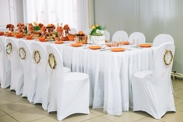 Decorative wreath on white chairs. Chairs and table covered with