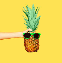 Fashion pineapple with sunglasses on yellow background, hand hol