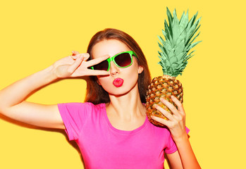 Fashion portrait cool girl in sunglasses and pineapple over yell