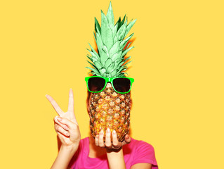 Fashion portrait woman and pineapple with sunglasses over yellow