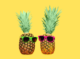 Two pineapple with sunglasses on yellow background, colorful ana