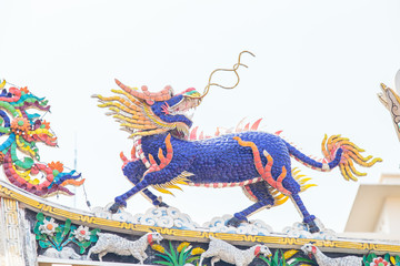 Colorful kirin statue in roof of chinese temple, powerful oriental legendary creature animal.
