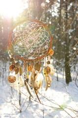 Handmade colorfull dream catcher in the snowy forest