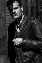 Handsome man portrait in the shadows wearing leather jacket