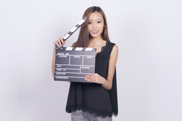 Happy asian woman holding a cinema clapper board.
