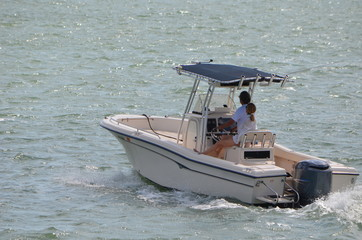 Young couple on a pleasure cruise in a small fishing boat powered by a single outboard engine.