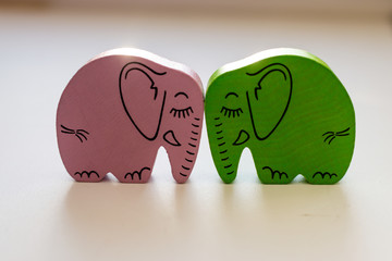 Pink and Green Wooden Elephants Touching Heads