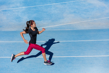 Athlete runner running on athletic track training her cardio. Jogger woman jogging at fast pace for competition race on blue lane at summer outdoor stadium wearing red capri tights and sports shoes.