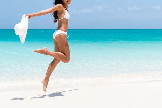 Beach ready bikini body - sexy slim legs and toned thighs and butt. Suntan happy woman jumping in freedom on white sand with sun hat. Weight loss success or epilation concept.