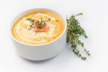 тыквенный крем-суп с кусочками семги на белом фоне