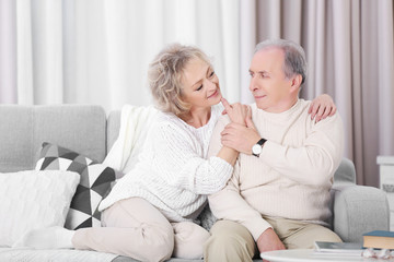 Happy mature couple sitting together on a sofa at home