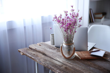 Modern interior. Comfortable workplace. Wooden table with beautiful bouquet of flowers and laptop on it, close up