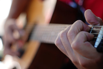 musician playing on an old acoustic guitar
