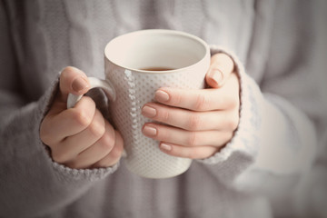 Woman in a grey knitted sweater holding a cup of tea in her hands, close up