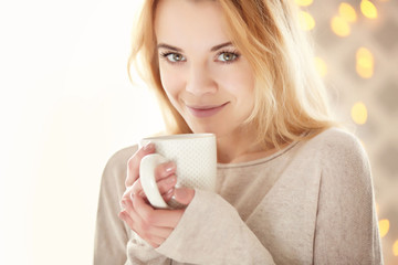Blonde beautiful smiling girl enjoying her cup of hot delicious coffee or tea on the light background