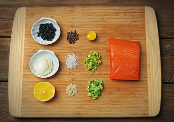 Tasty ingredients of salmon tartare on cutting board, flat lay