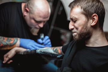 master tattooist makes a tattoo on the skin. The client narrows his eyes and turns away, the concept of pain and fear